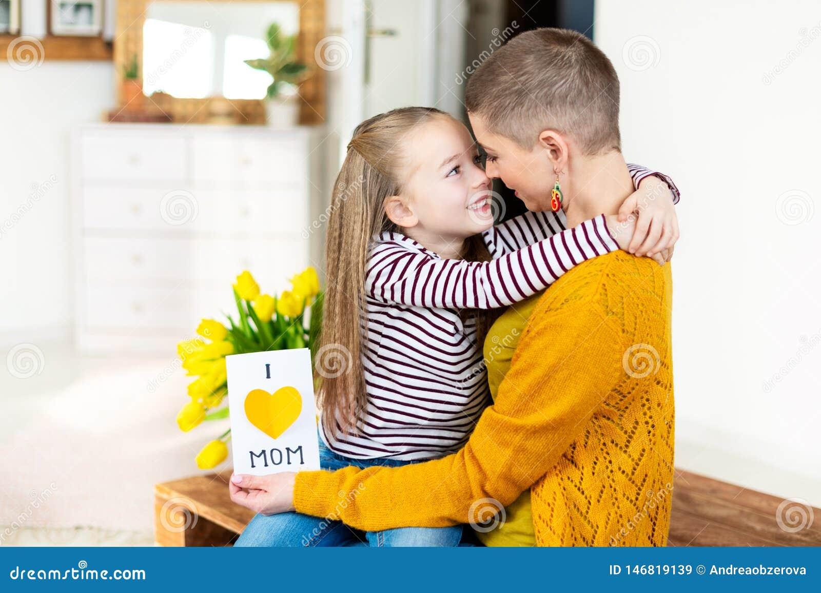 Прелестная маленькая девочка давая ее маму, молодой онкологический больного, домодельный Я ЛЮБЛЮ поздравительную открытку МАМЫ Сч