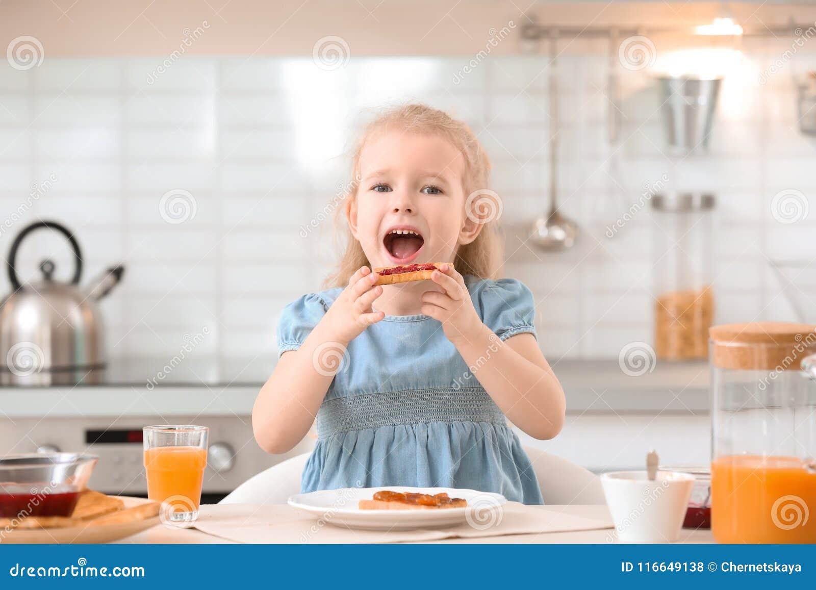 Прелестная маленькая девочка есть вкусный провозглашанный тост хлеб с вареньем