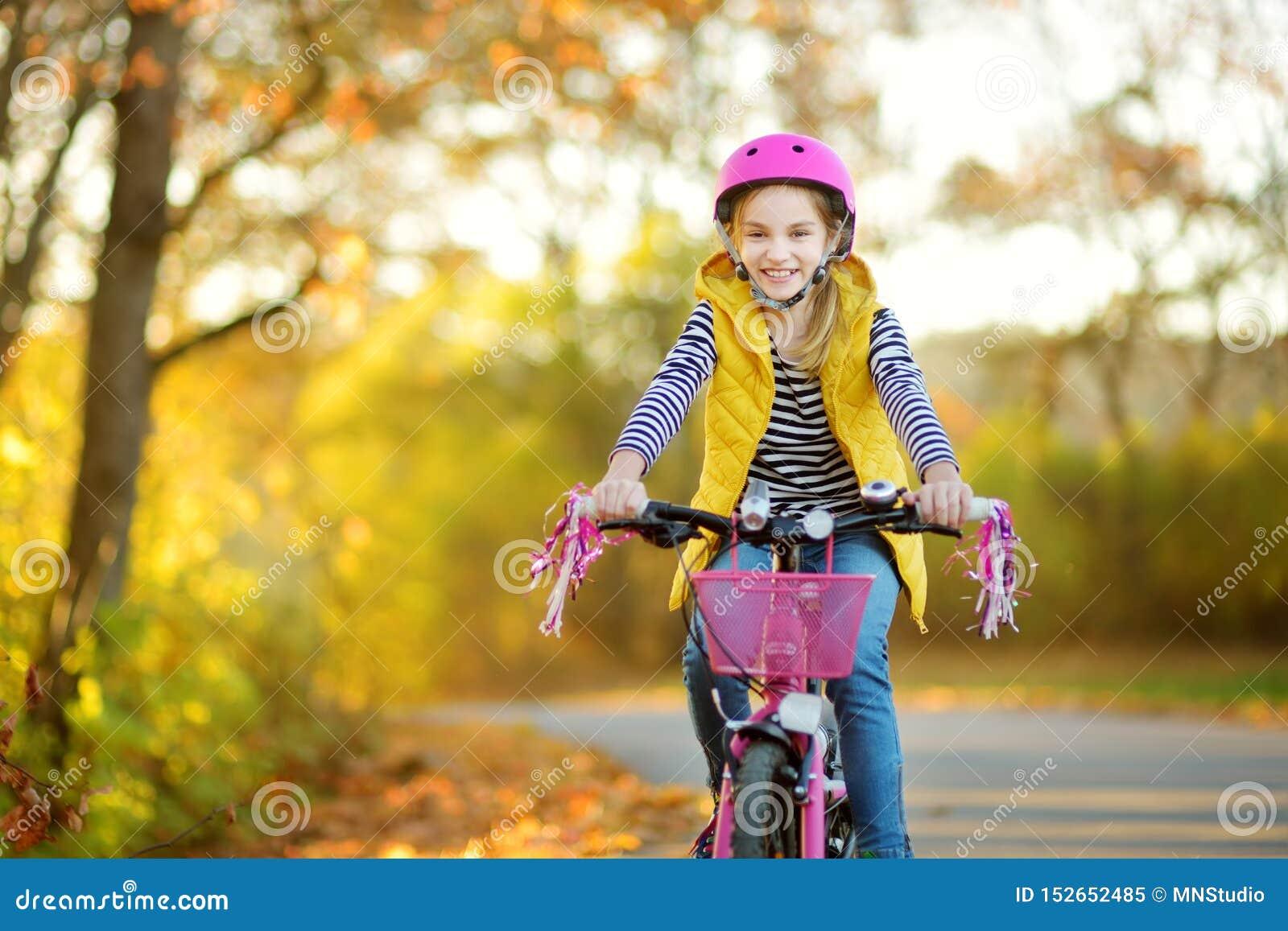 Прелестная маленькая девочка ехать велосипед в парке города на солнечный день осени Активный отдых семьи с детьми