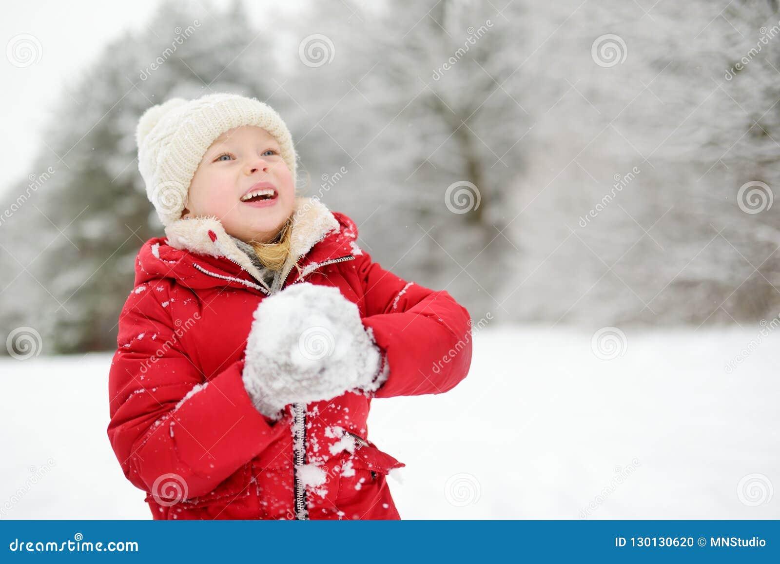 Прелестная маленькая девочка имея потеху в красивом парке зимы Милый ребенок играя в снеге
