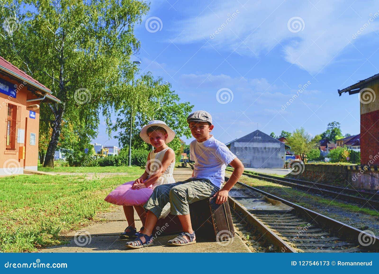 Прелестная маленькая девочка и мальчик на железнодорожном вокзале, ждать поезд с винтажными чемоданами Путешествовать, праздник и