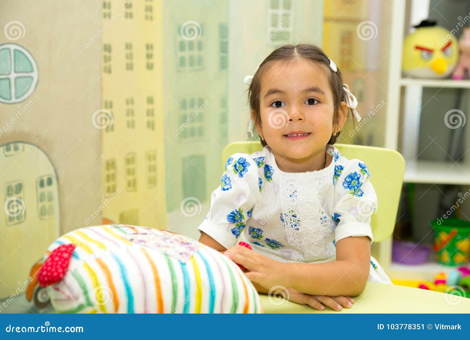Прелестный азиат, девушка ребенка казаха в комнате питомника Ребенк в детском саде в классе preschool Montessori