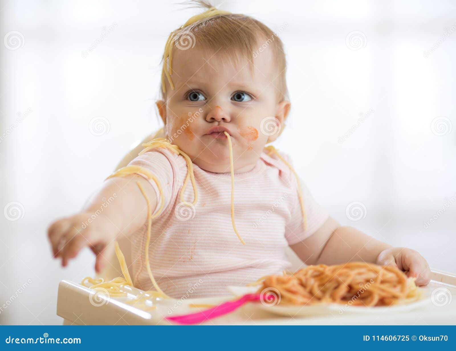 Прелестный маленький младенец один год есть макаронные изделия крытые Смешной ребенок малыша с спагетти Милый ребенк и здоровая е