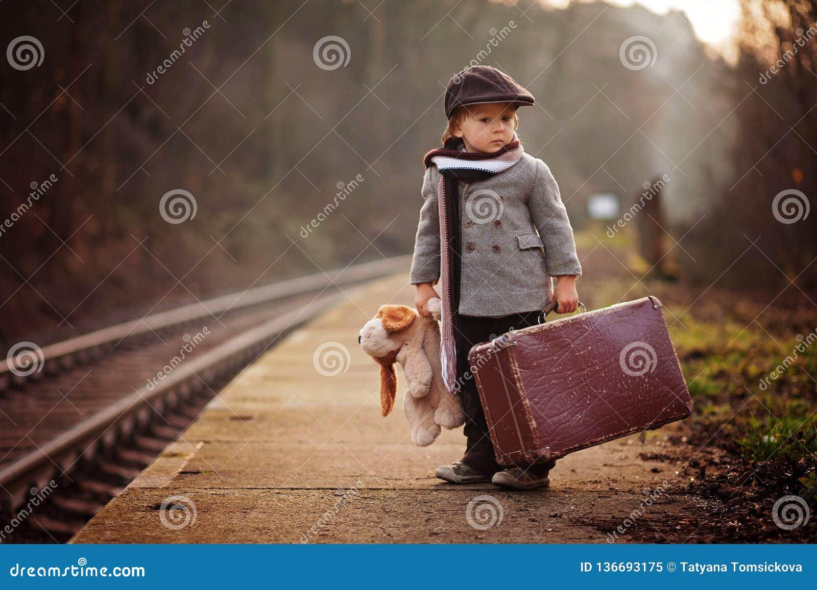 Прелестный мальчик на железнодорожном вокзале, ждать поезд с чемоданом и плюшевым медвежонком