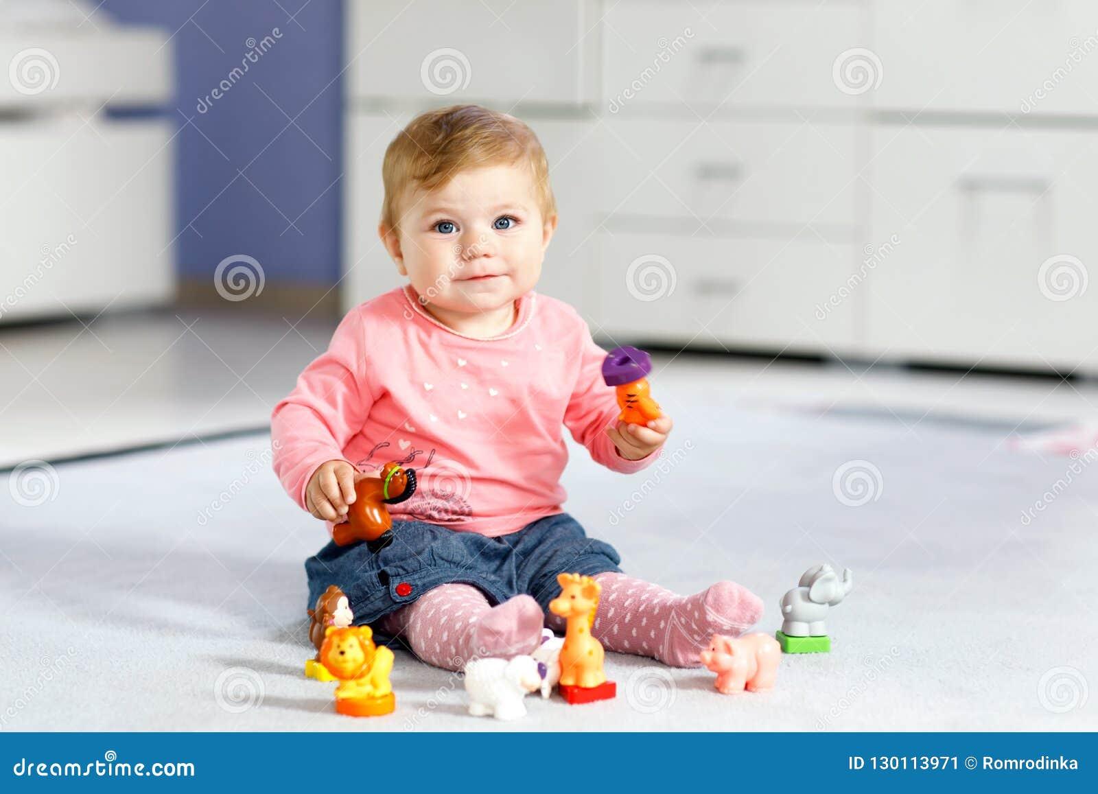 Прелестный ребёнок играя с отечественными любимчиками игрушки как корова, лошадь, овцы, собака и дикие животные любят жираф, слон