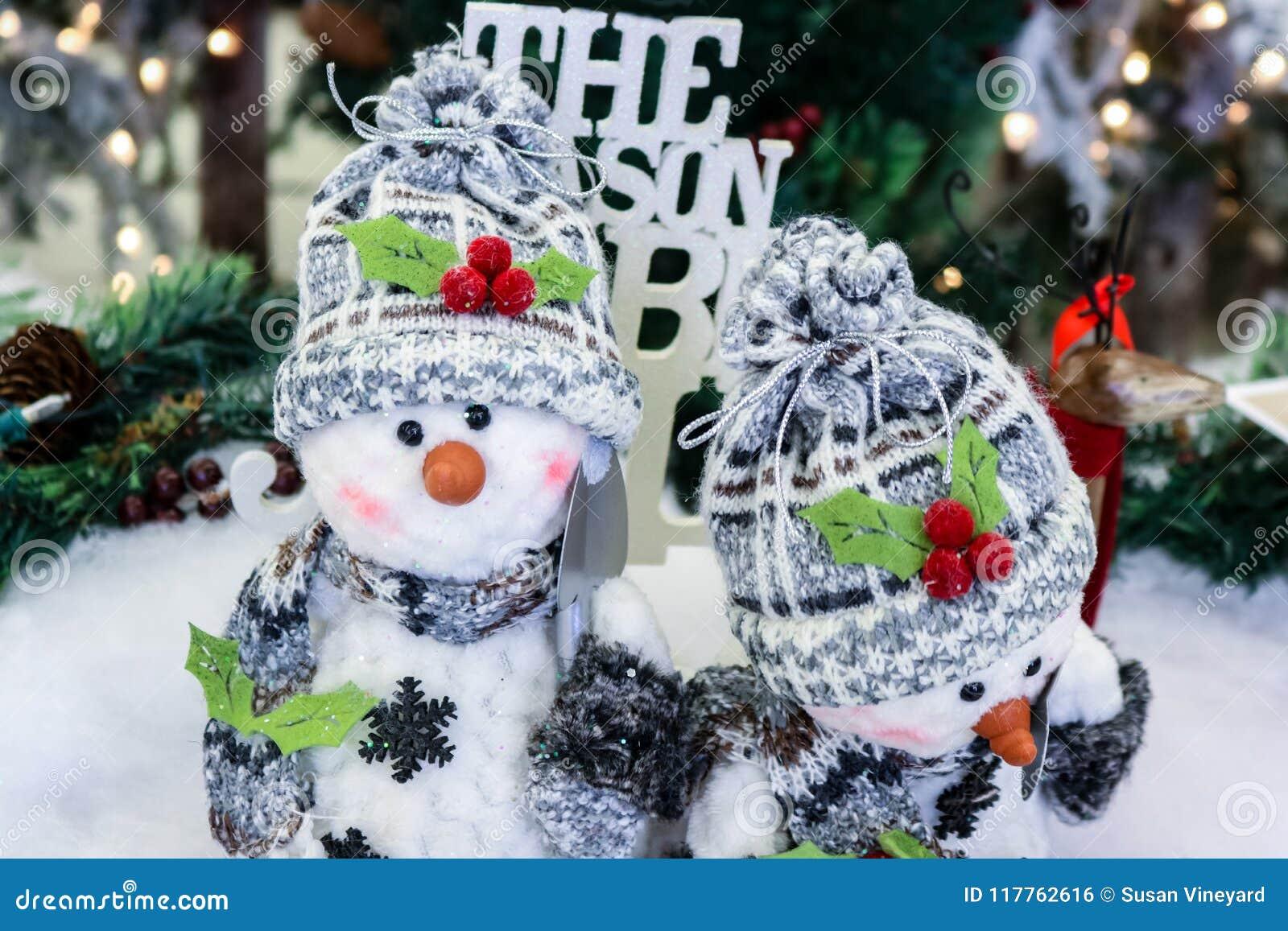 2 прелестных орнаментальных снеговика с снегом копают крышки и шарфы перед запачканной предпосылкой рождества