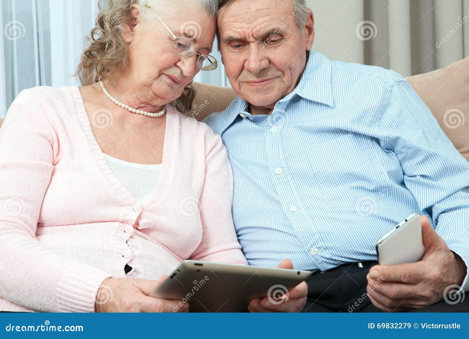 Престарелый Пожилые пары держа компьтер-книжку, smartphone и делают приобретения над интернетом в уютной живущей комнате hous