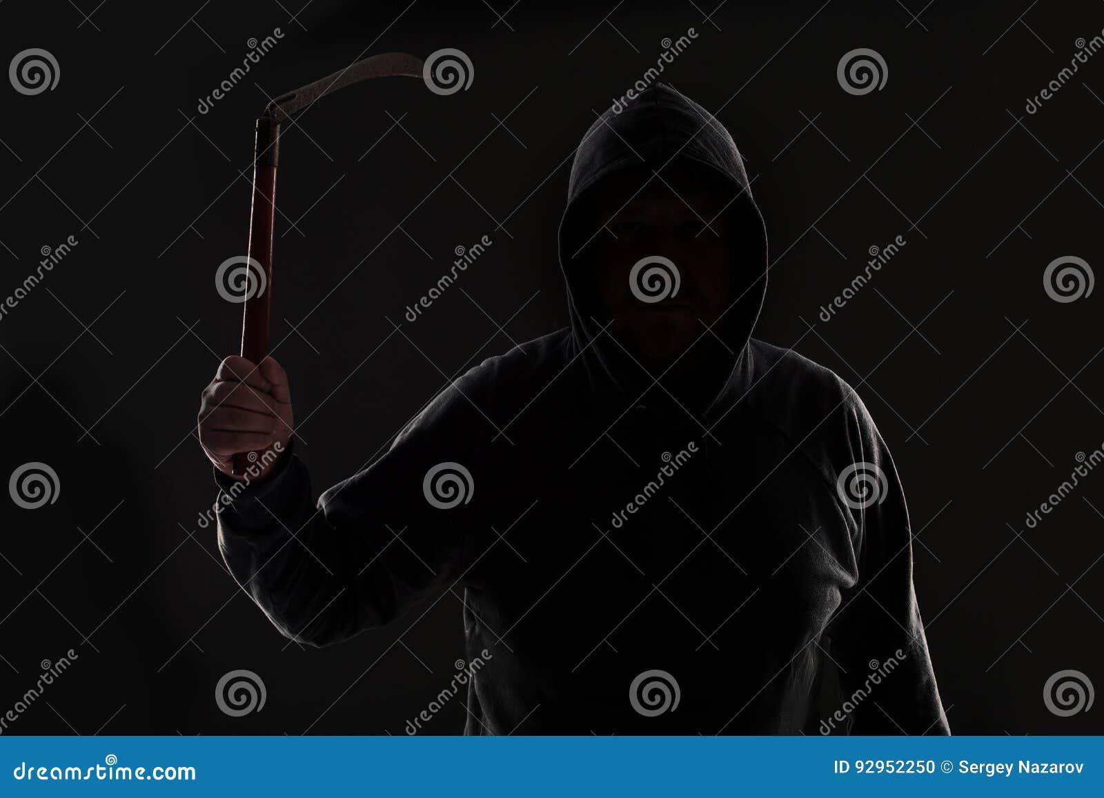 Преступник в темных одеждах и балаклаве с косой