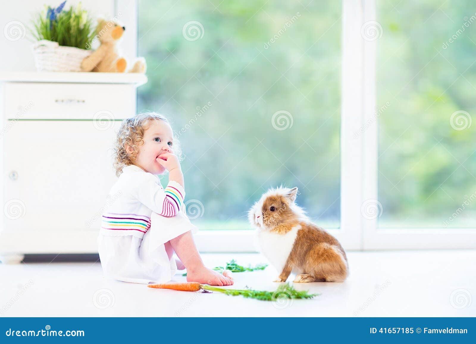 Прелестная девушка малыша играя с реальным зайчиком