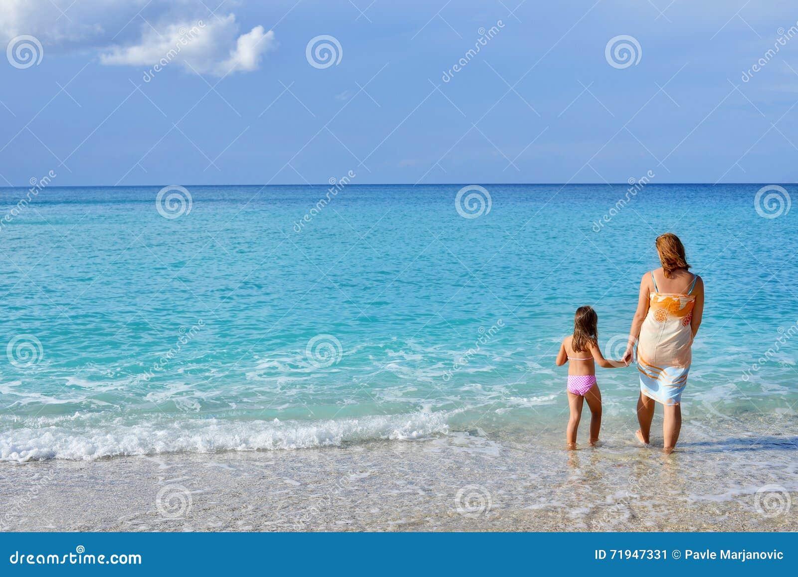 Прелестная девушка малыша наслаждаясь ее летними каникулами на пляже с