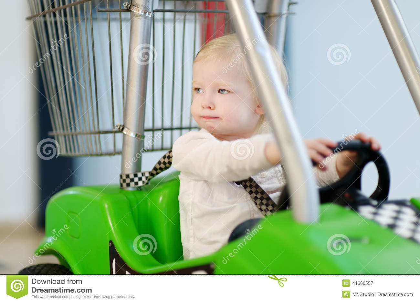 Прелестная девушка сидя в магазинной тележкае