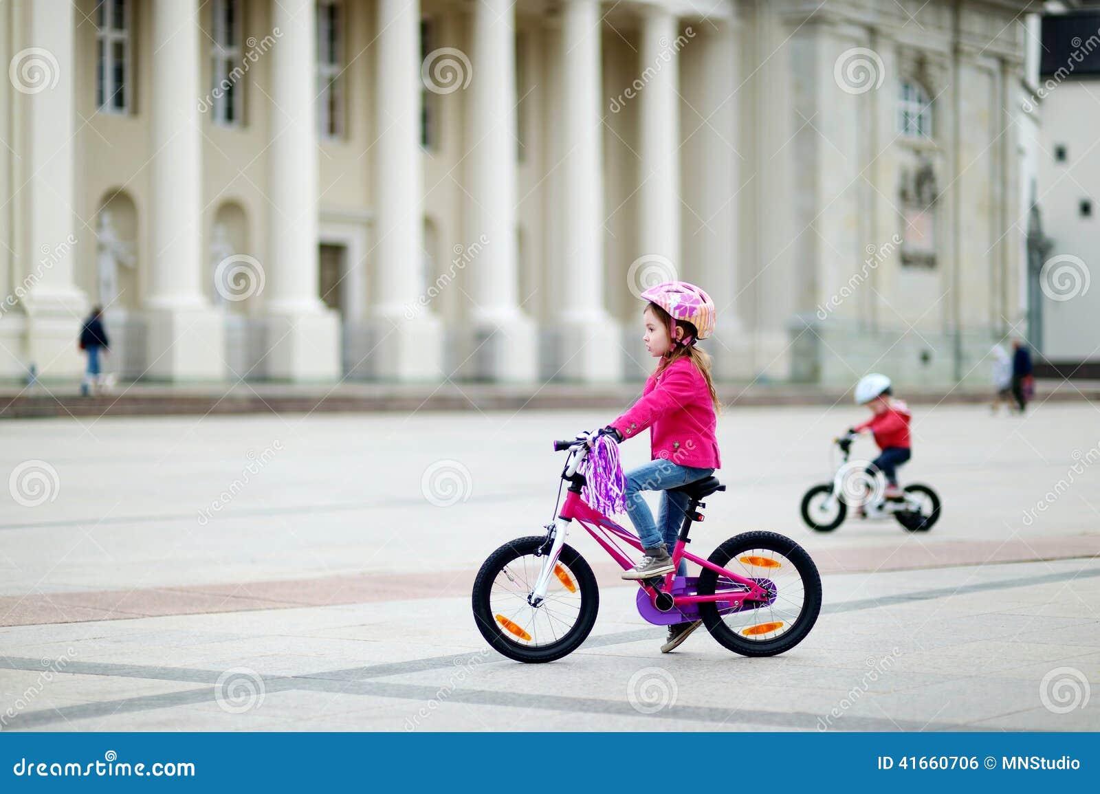 Прелестная маленькая девочка ехать велосипед