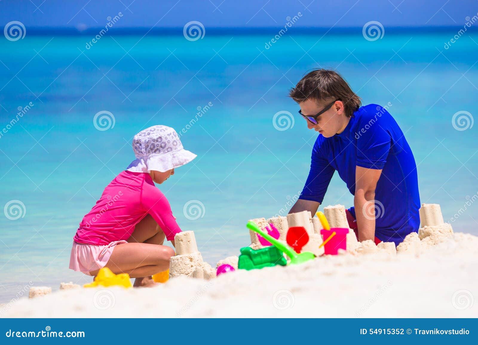 Прелестная маленькая девочка и счастливый папа играя с