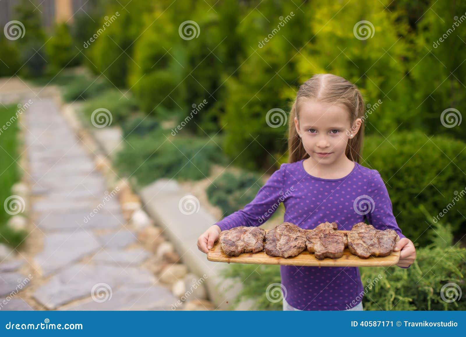 Прелестная маленькая девочка с зажаренными стейками в руках внешних
