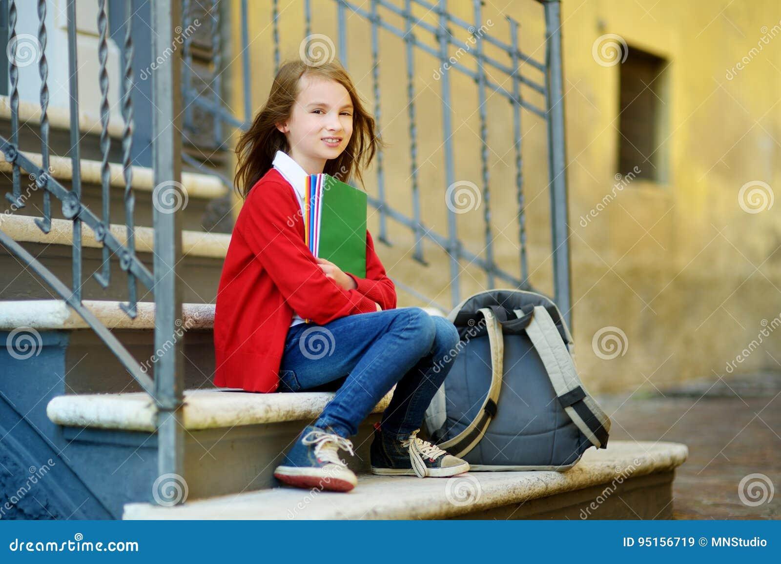 Прелестная маленькая школьница изучая outdoors на яркий день осени Молодой студент делая ее домашнюю работу Образование для малых