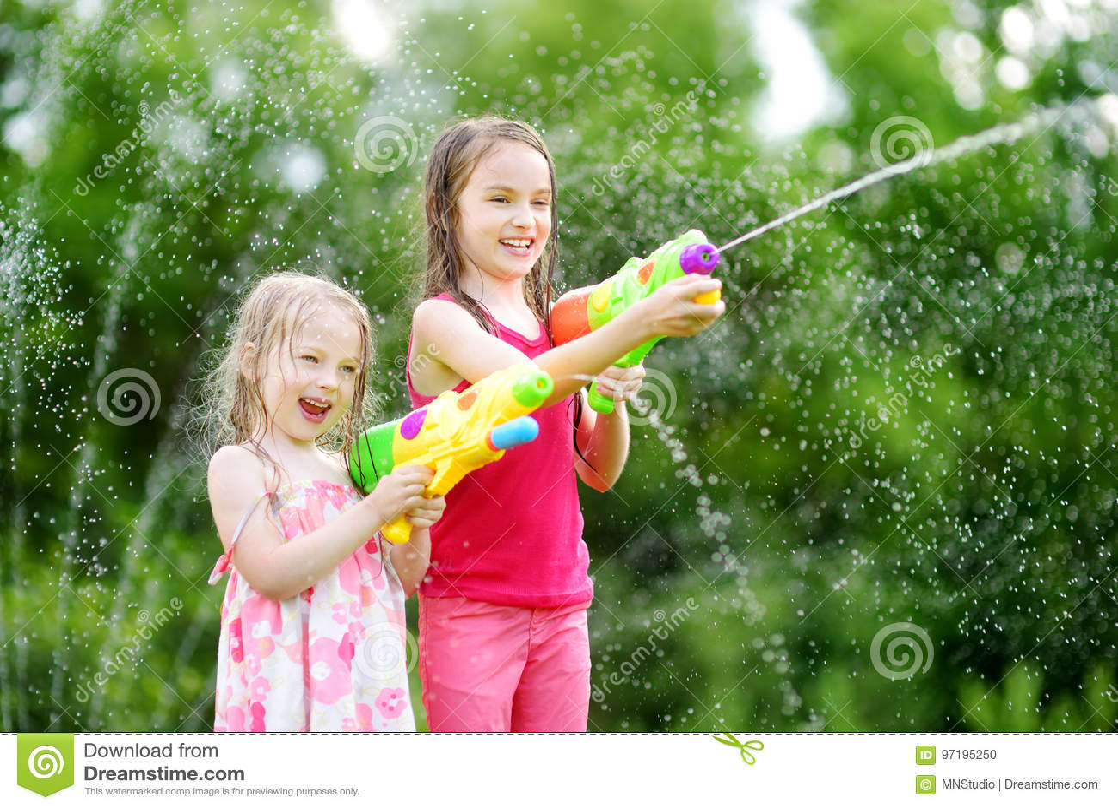 Прелестные маленькие девочки играя с водяными пистолетами на горячий летний день Милые дети имея потеху с водой outdoors