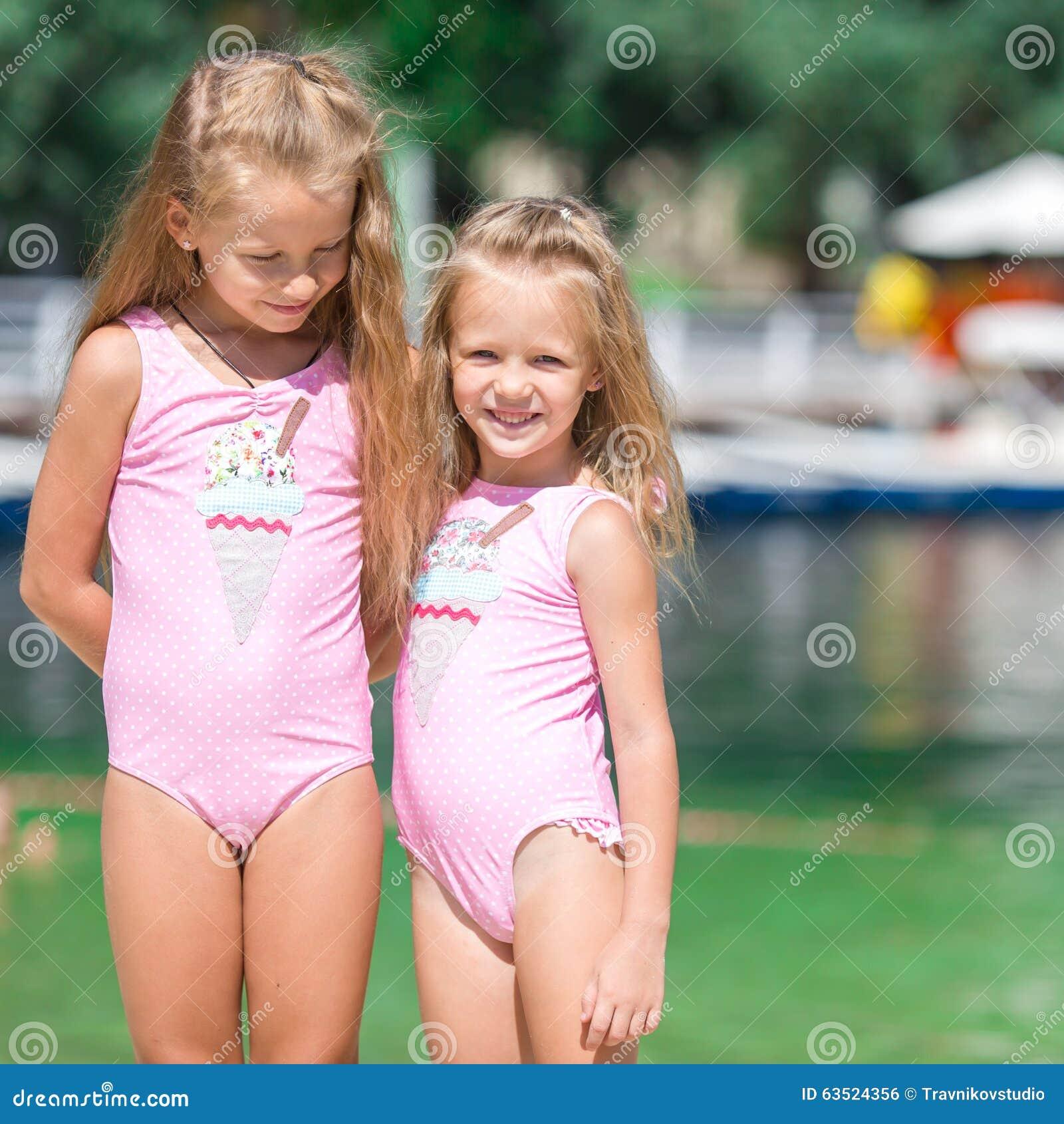 маленькие девочки Прелестные маленькие девочки имея потеху во время пляжа