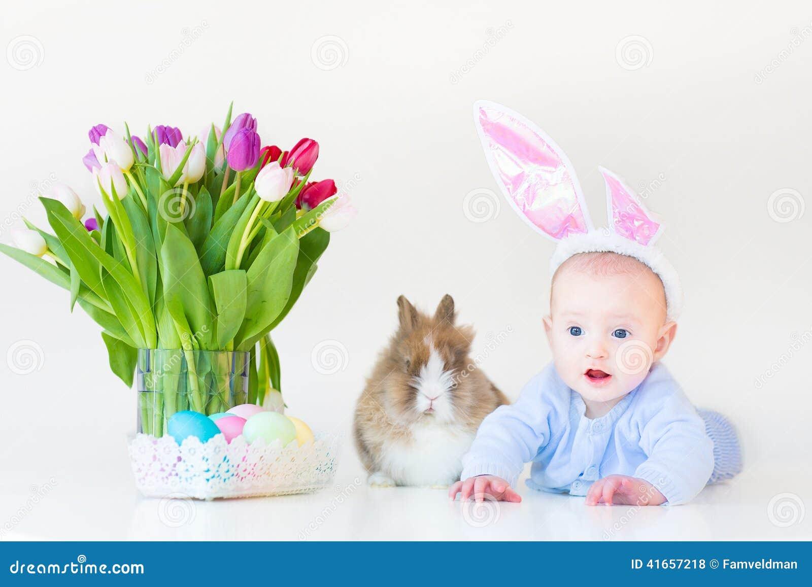 Прелестный ребёнок с ушами зайчика с реальным кроликом