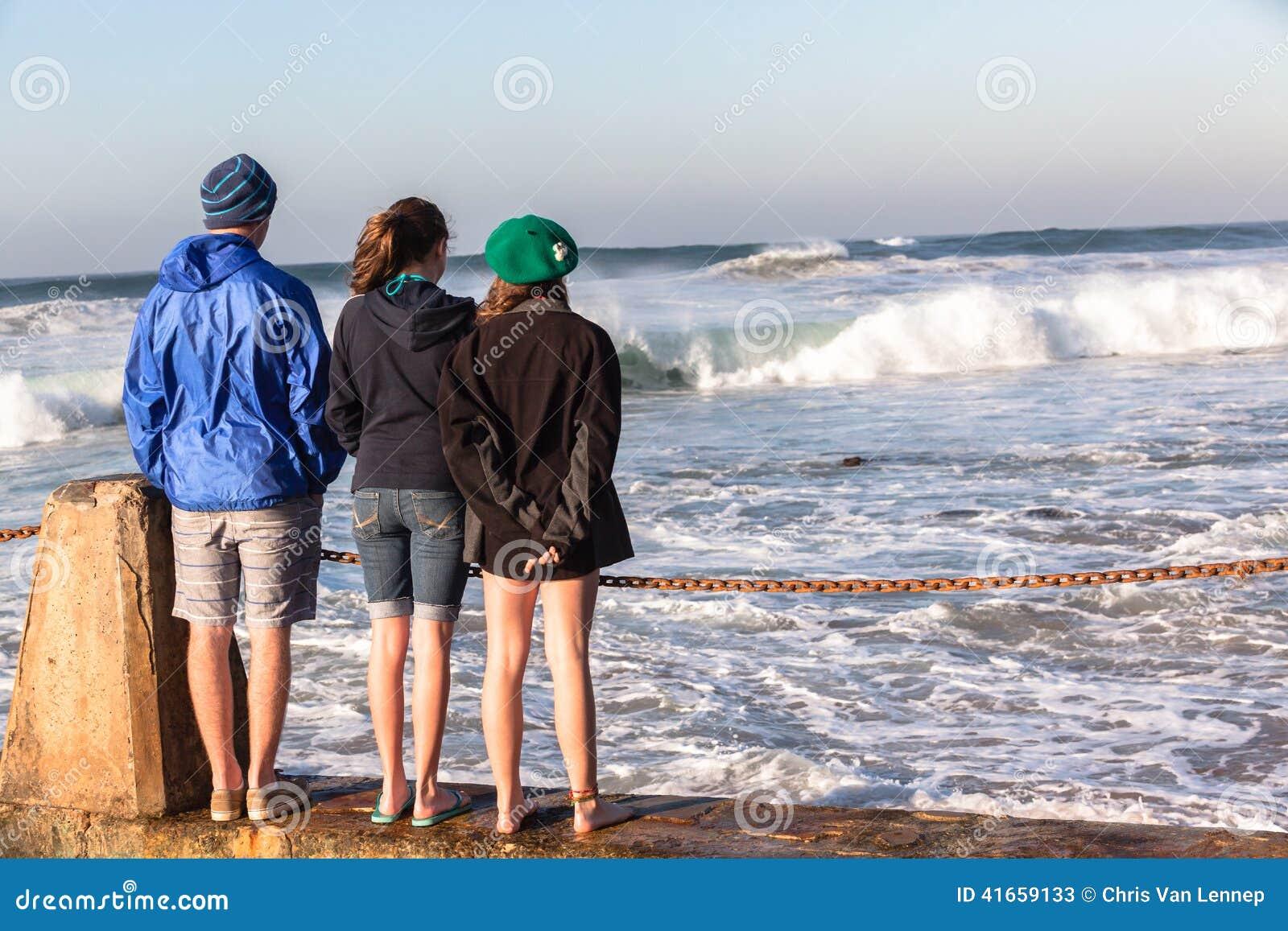 Предназначенные для подростков волны пляжа девушек мальчика