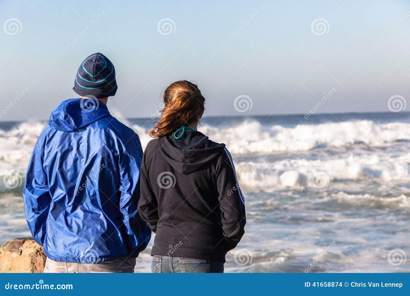 Предназначенные для подростков волны пляжа девушки мальчика