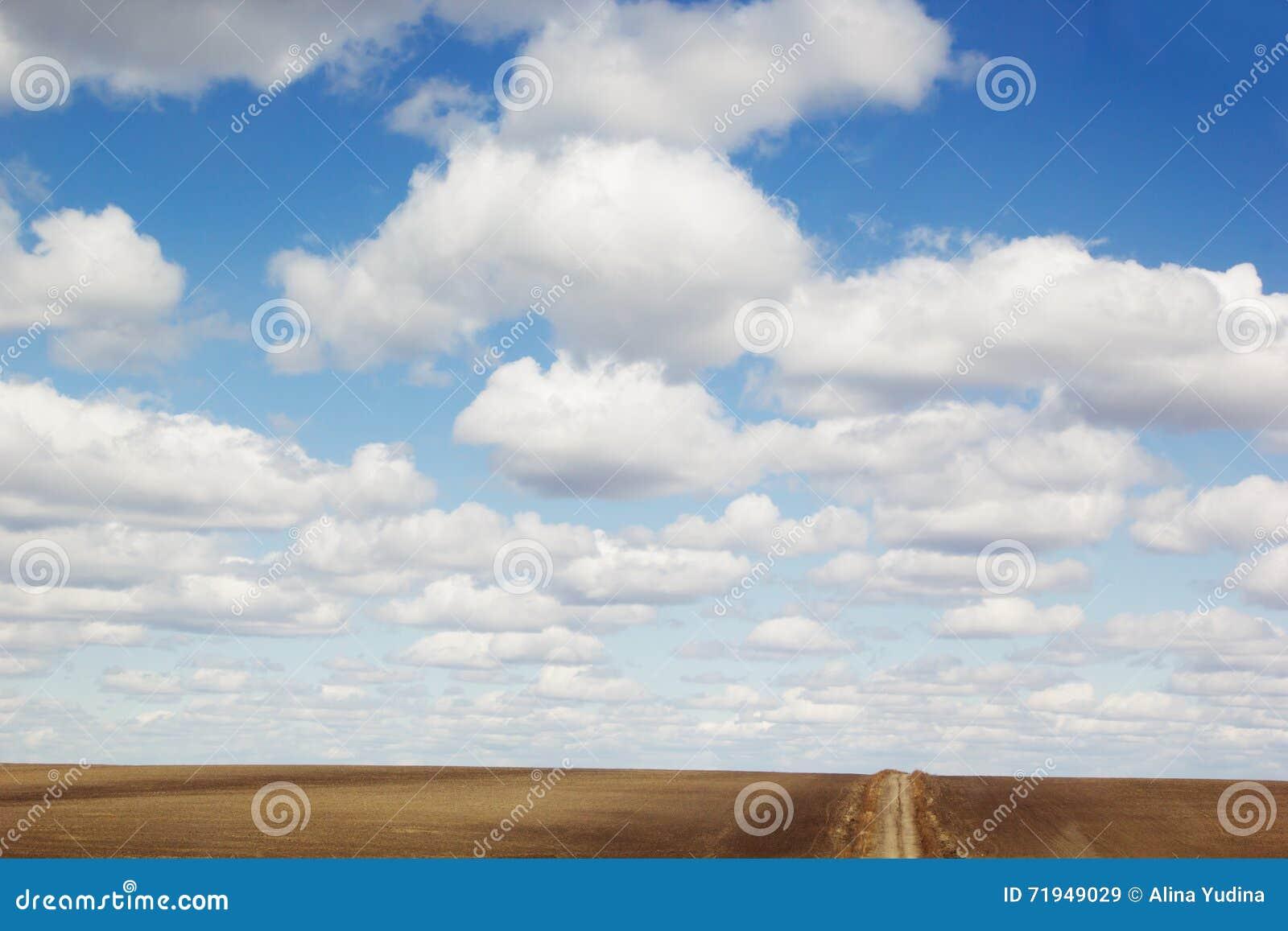 Предпосылка голубого неба с мягкими шелковистыми облаками, полем прокладки и дорогой