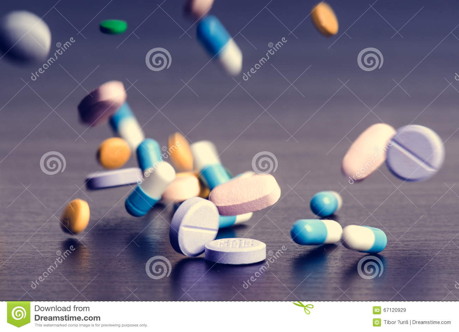 Предпосылка фармации на темной таблице Пилюльки левитации Таблетки на темной предпосылке которая падая вниз Пилюльки Медицина и з