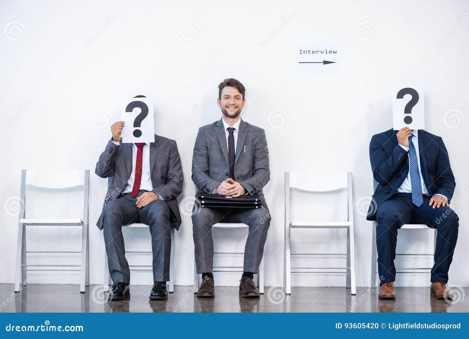 Предприниматели сидя в очереди и ждать интервью, держа вопросительные знаки в офисе