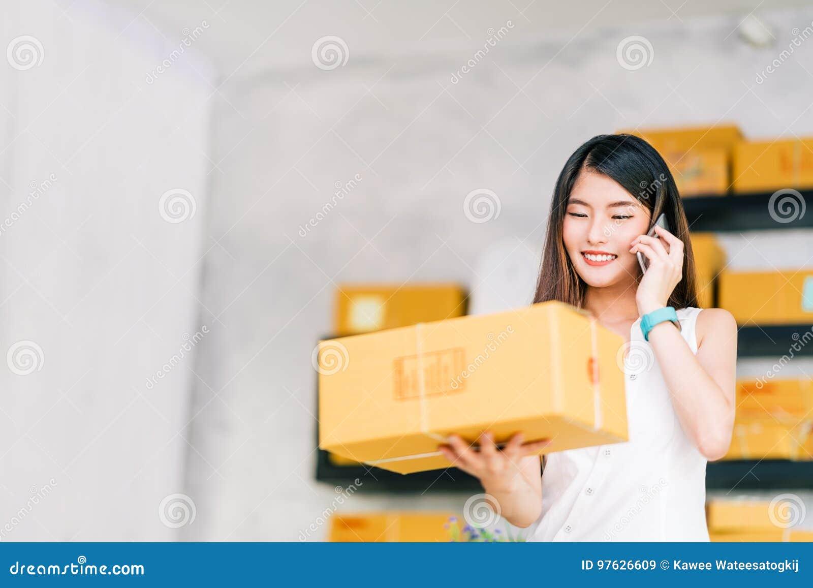Предприниматель мелкого бизнеса, азиатская коробка пакета владением женщины, используя звонок мобильного телефона получая заказ н