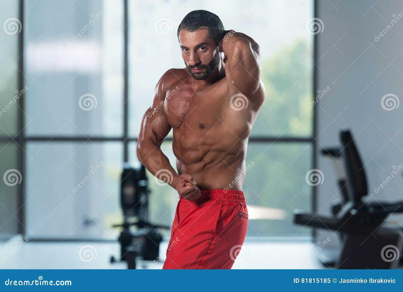 Представление комода мышц молодого культуриста изгибая бортовое