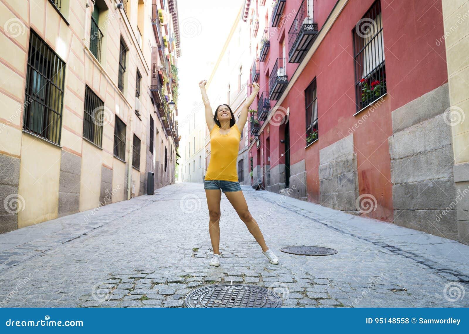 Представлять молодой привлекательной латинской женщины счастливый и excited на современном городском европейском городе