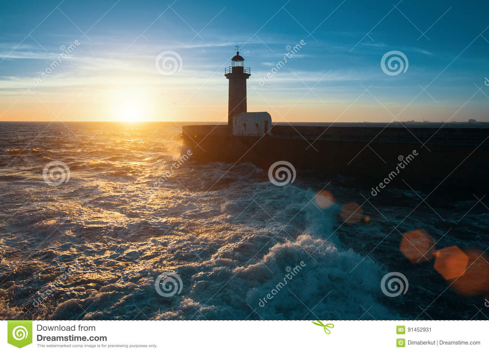 Прибой океана на атлантическом побережье, около маяка во время красивого захода солнца, Порту