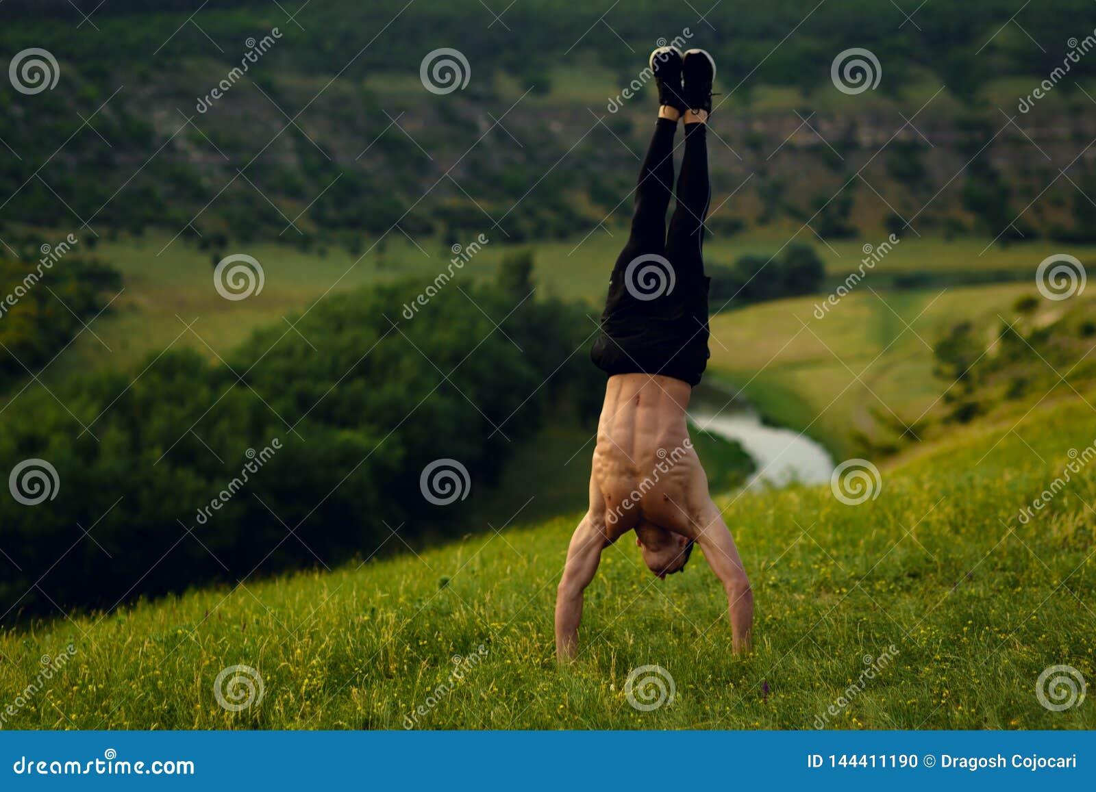 Привлекательная без рубашки внешняя сторона стойки молодого человека пригонки показывая 6 abs пакета на предпосылке ландшафта лес