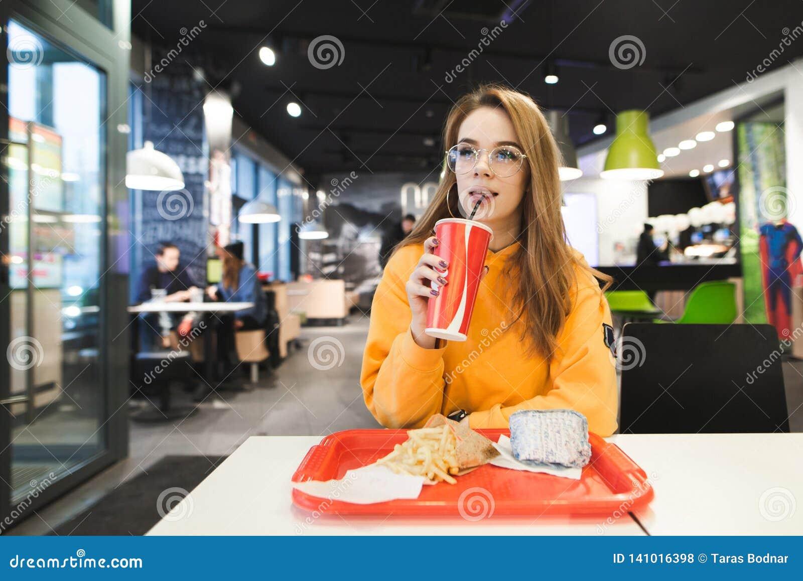 Привлекательная девушка в стеклах сидя в ресторане фаст-фуда с подносом французских картофеля фри и бургера и колы напитка