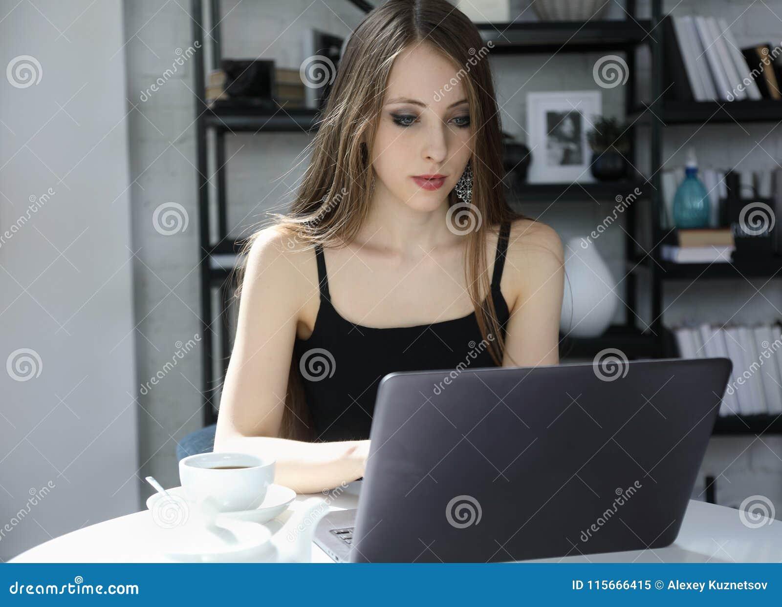 Привлекательная девушка работая на компьтер-книжке внутри помещения