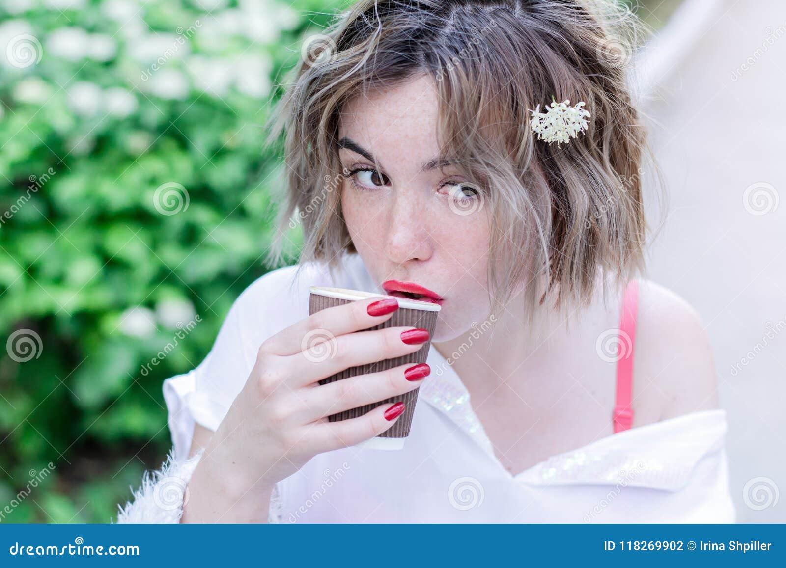 Привлекательная девушка с красными губами и цветком whith маникюра в ее волосах сидит в парке и выпивая кофе
