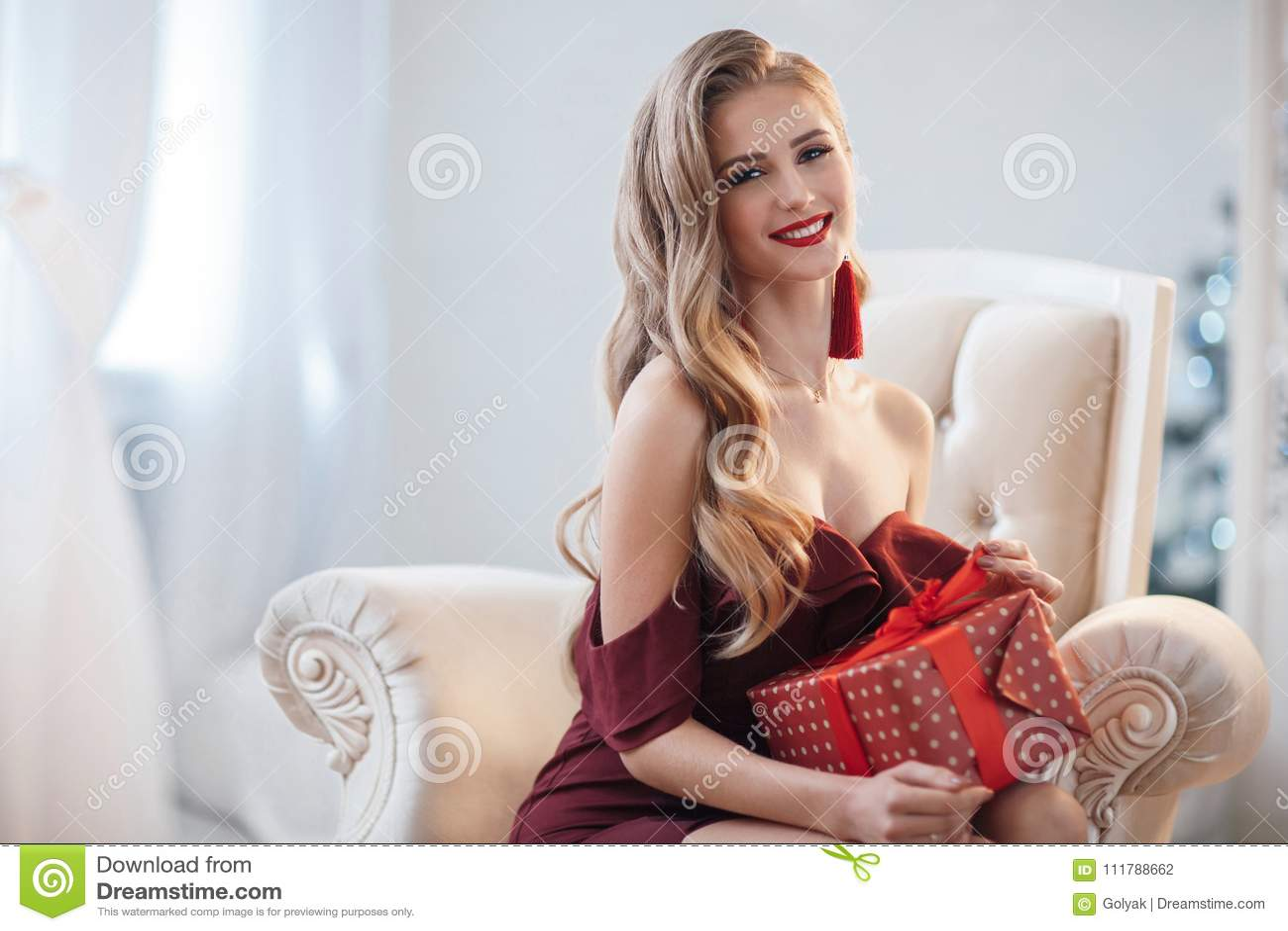 Привлекательная женщина в открытом, бургундском платье, сидя в шикарном стуле, в яркой домашней комнате, раскрывает подарок