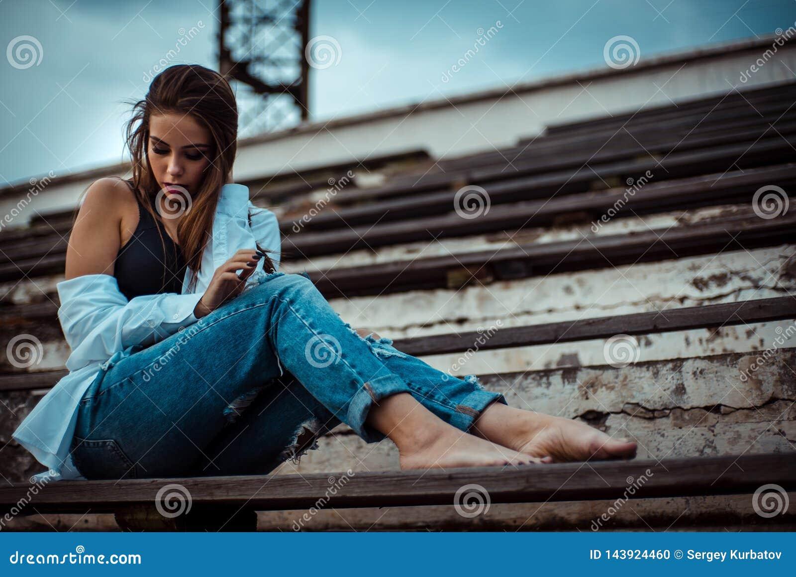 Привлекательная женщина сидя с босыми ногами в стадионе Она носит рубашку и джинсы