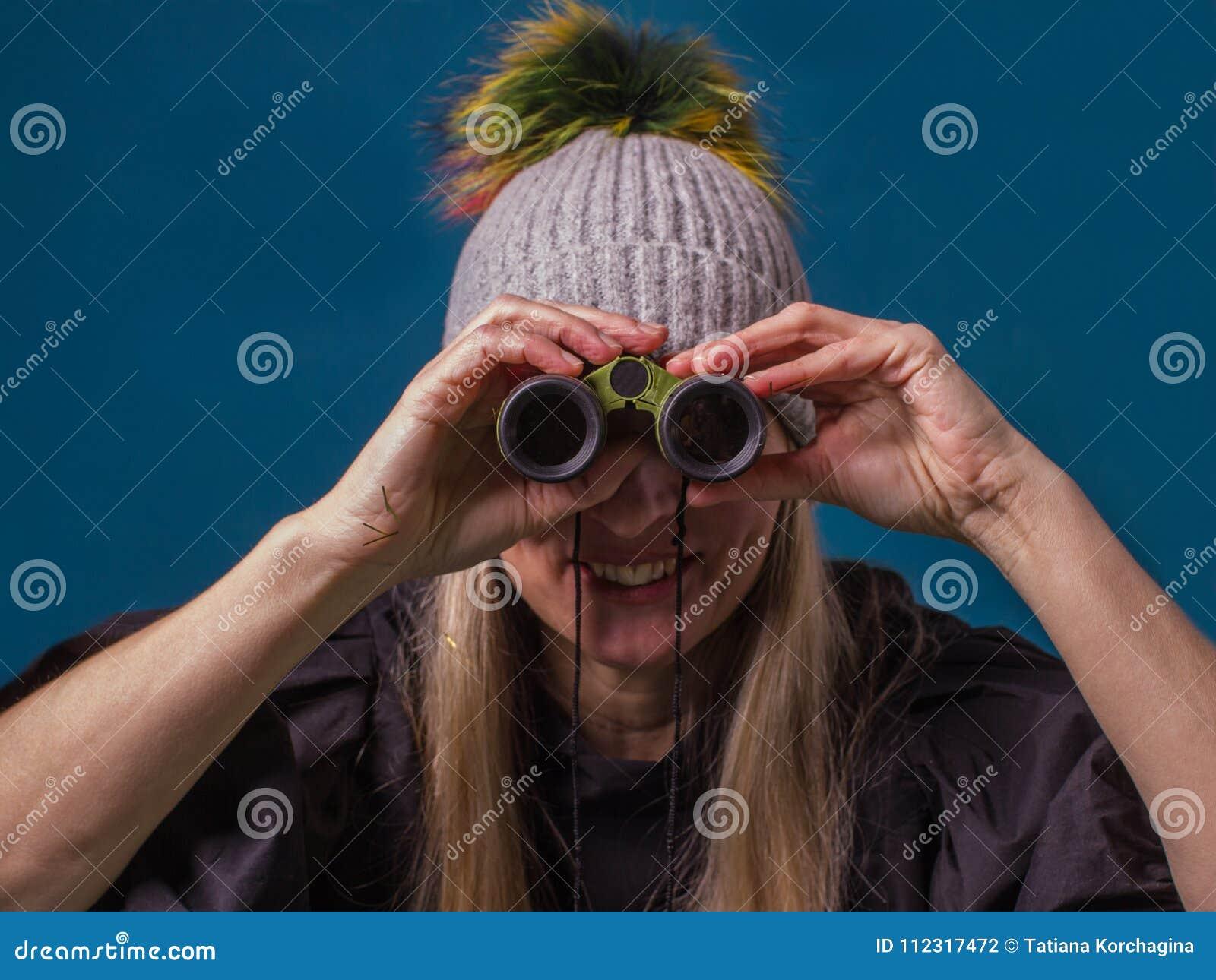 Привлекательная женщина смотря через бинокулярное Цель, будущее и