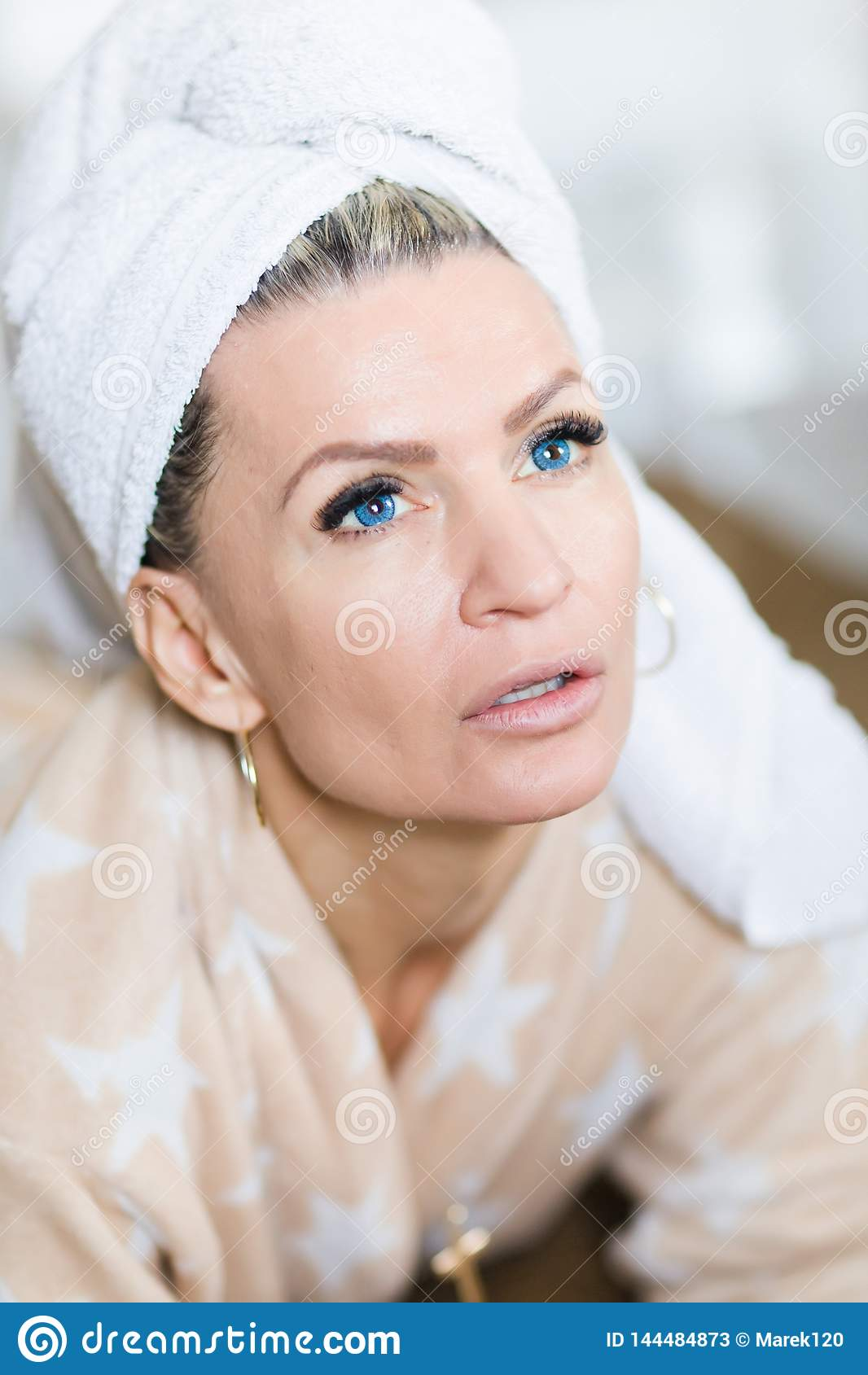 Привлекательная женщина с голубыми контактными линзами с полотенцем на голове после релаксации