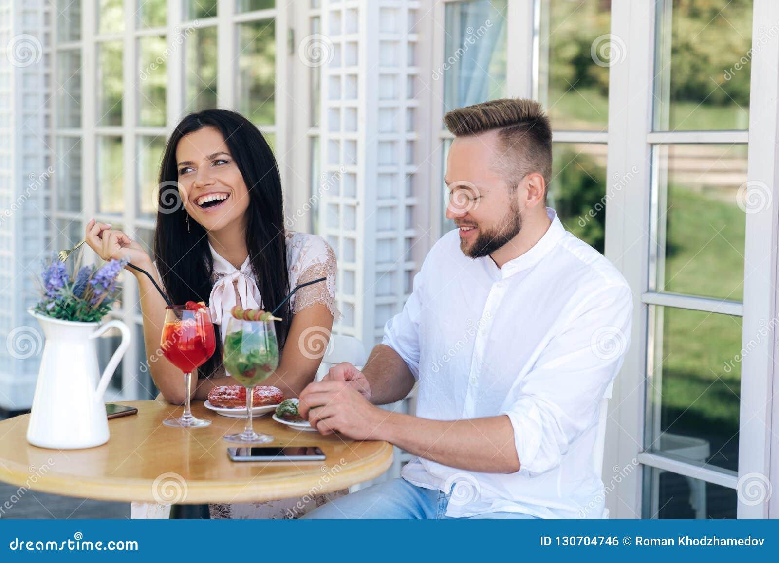 Привлекательная жизнерадостная девушка пришла увидеть славного стильного парня пара отдыхает в кафе, ел плашки, говоря и