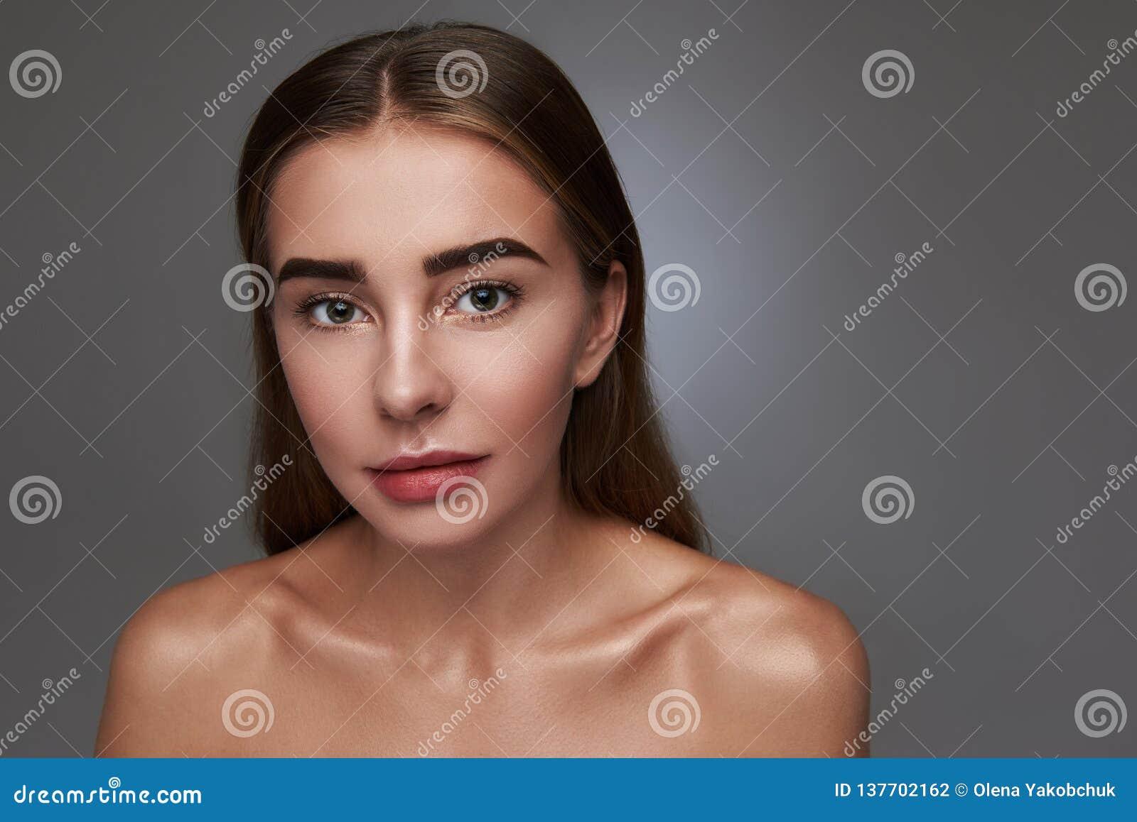 Привлекательная молодая женщина представляя против серой предпосылки
