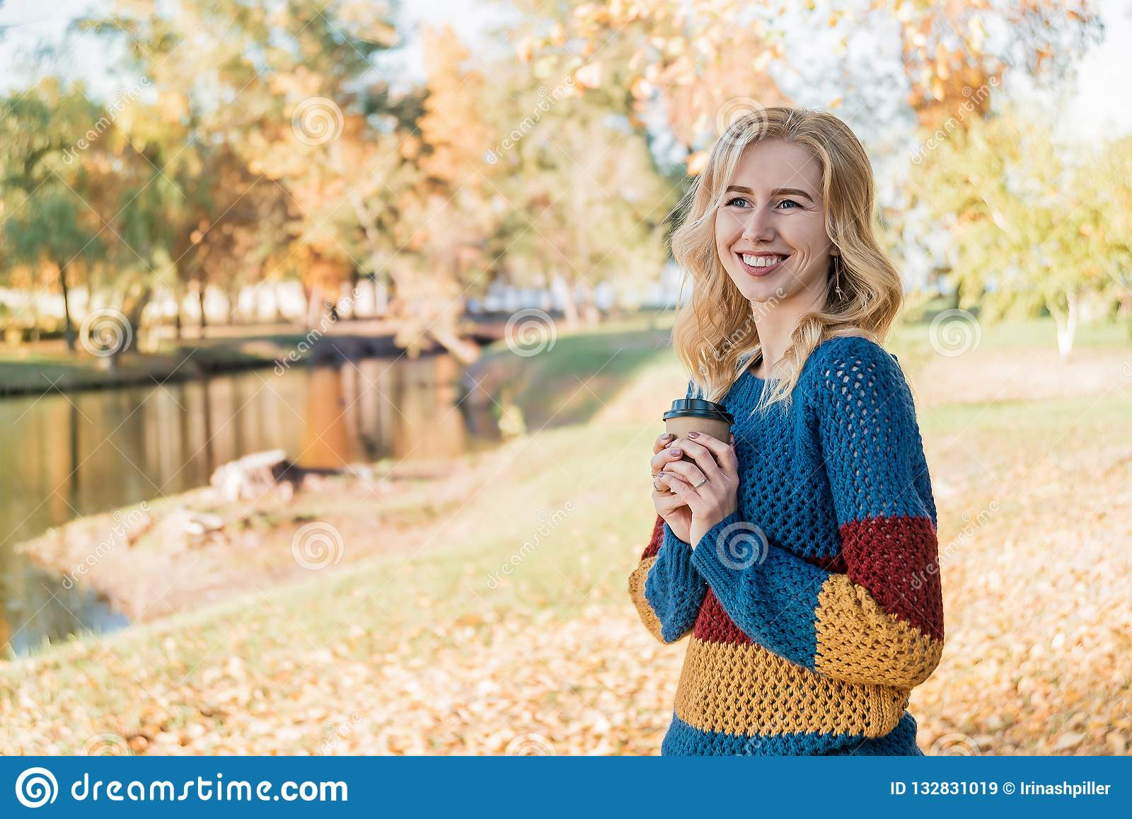 Привлекательная молодая женщина с кофе напитков вьющиеся волосы снаружи