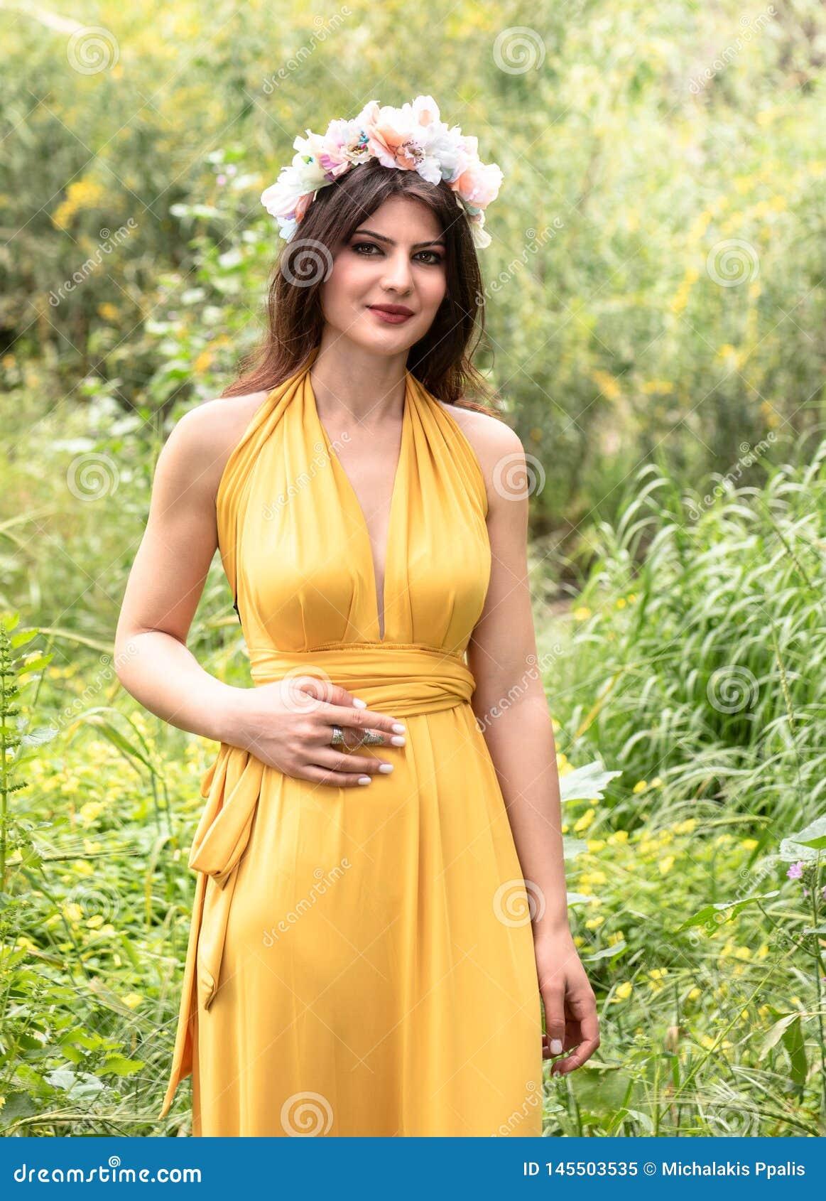 Привлекательная молодая красивая дама в зеленых полях