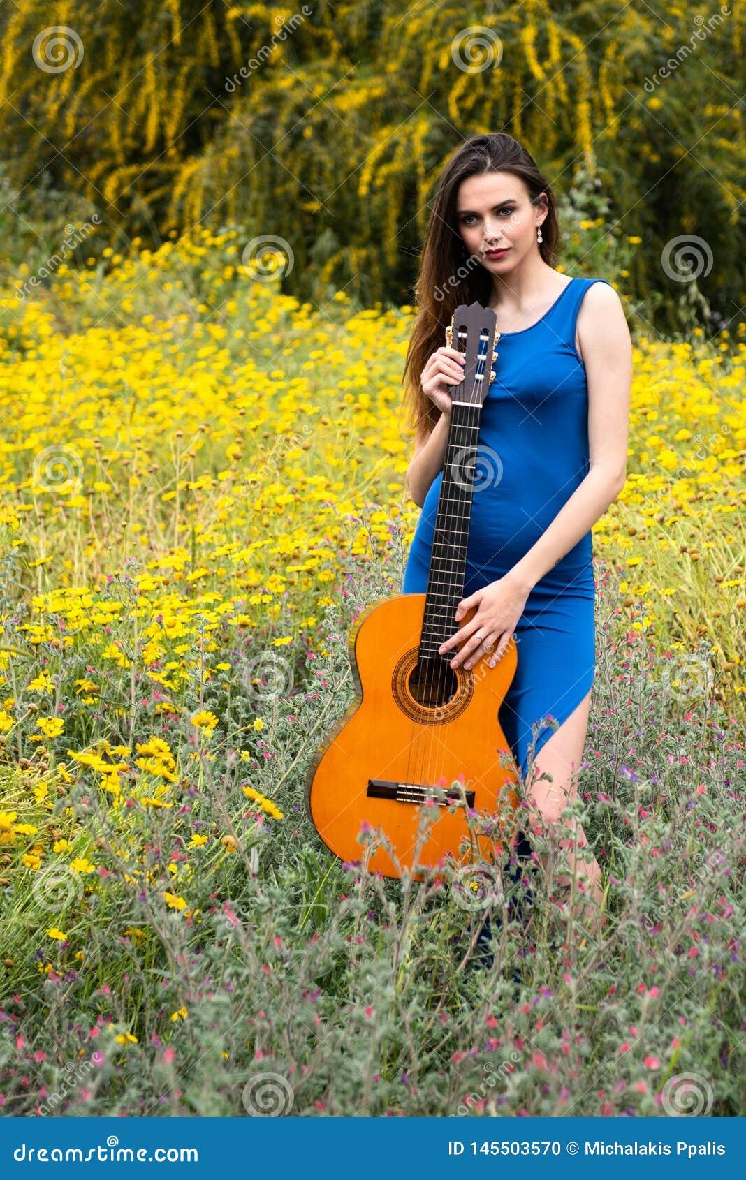 Привлекательная молодая красивая женщина держа классическую гитару