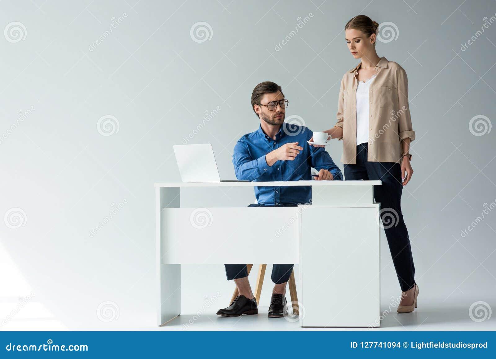 привлекательная молодая секретарша проходя чашку кофе для того чтобы хозяйничать