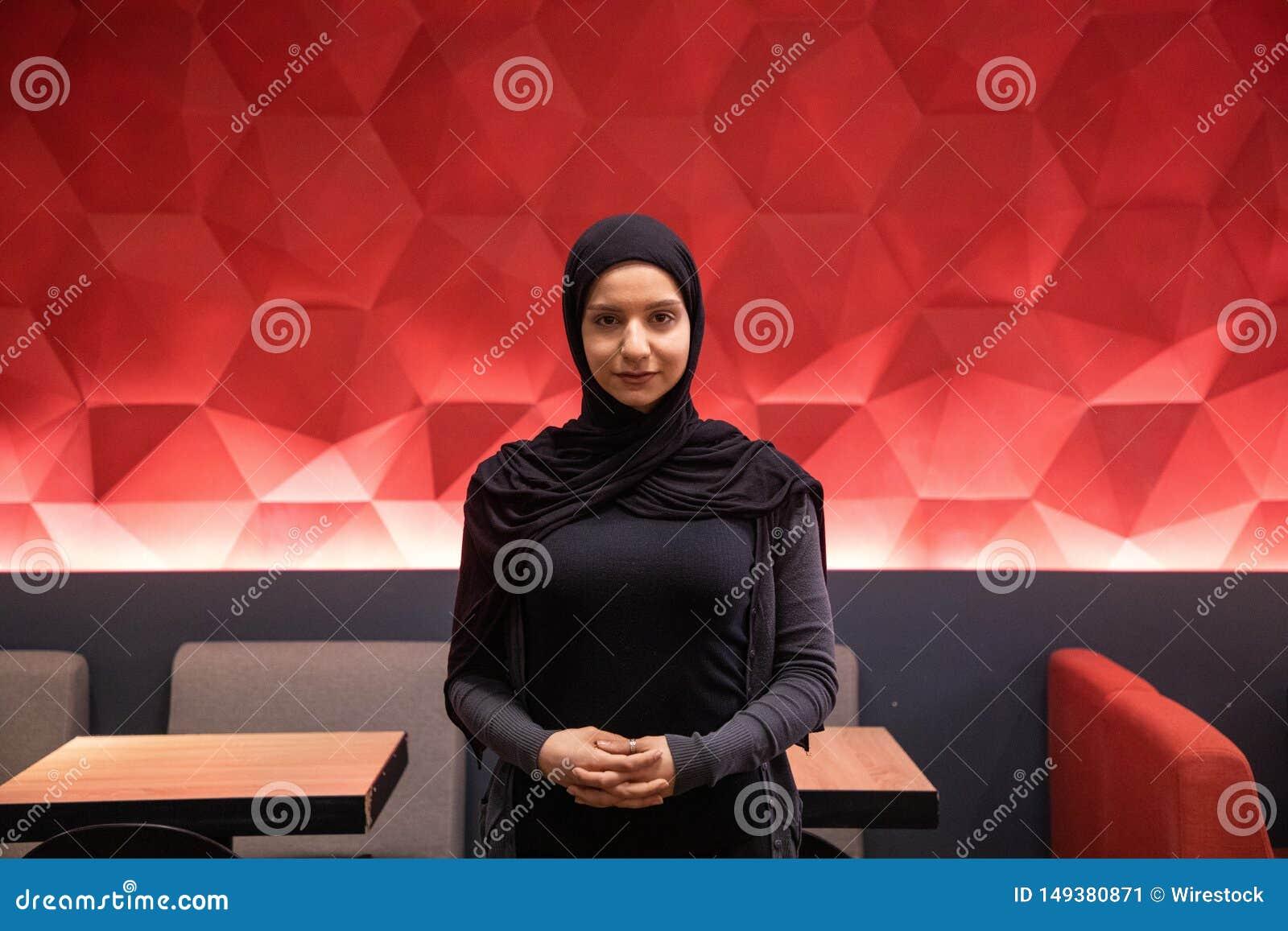 Привлекательная мусульманская женщина в черном hijab смотря камеру с красной крутой предпосылкой