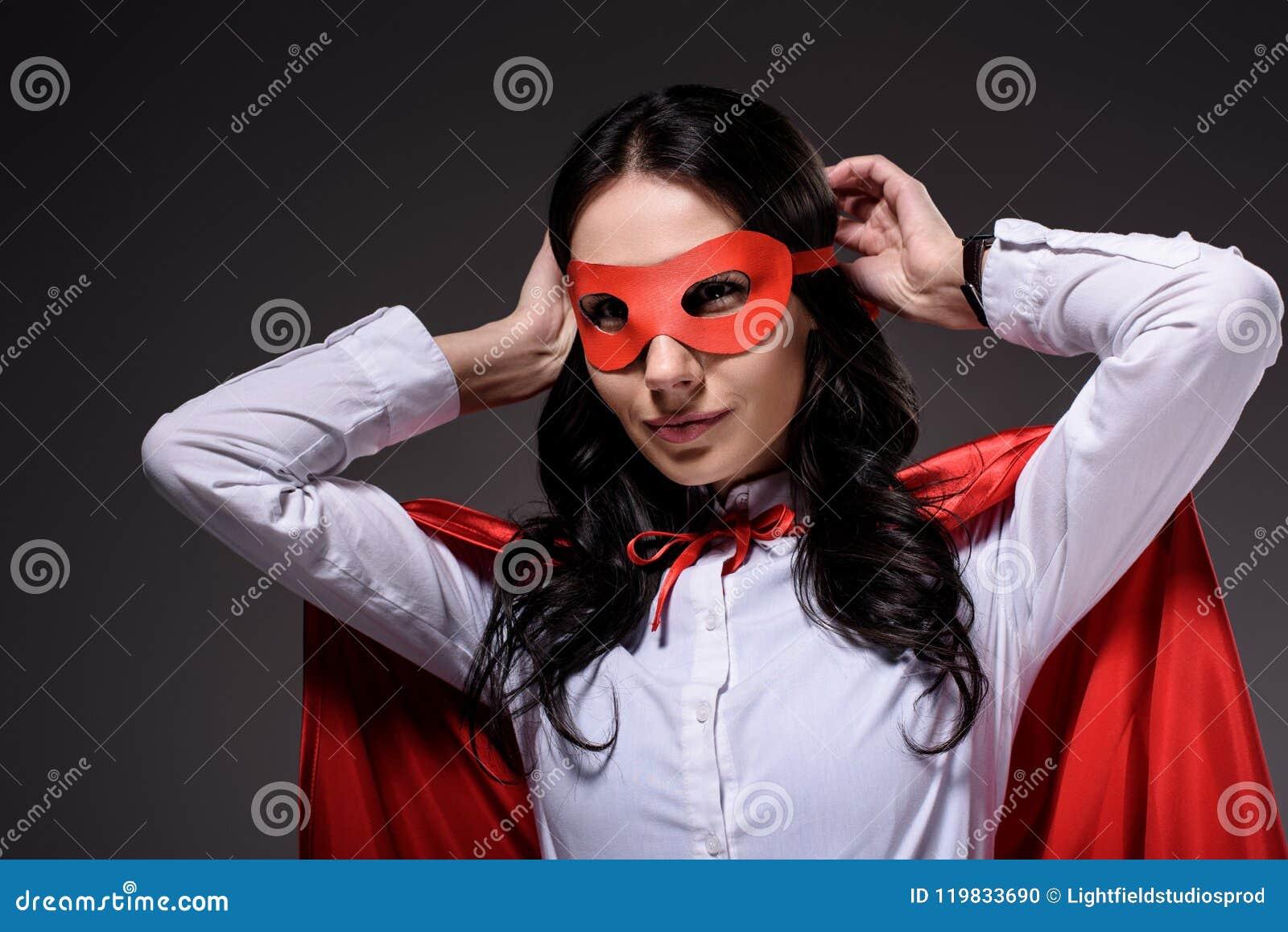 привлекательная супер коммерсантка в красной накидке связывая маску