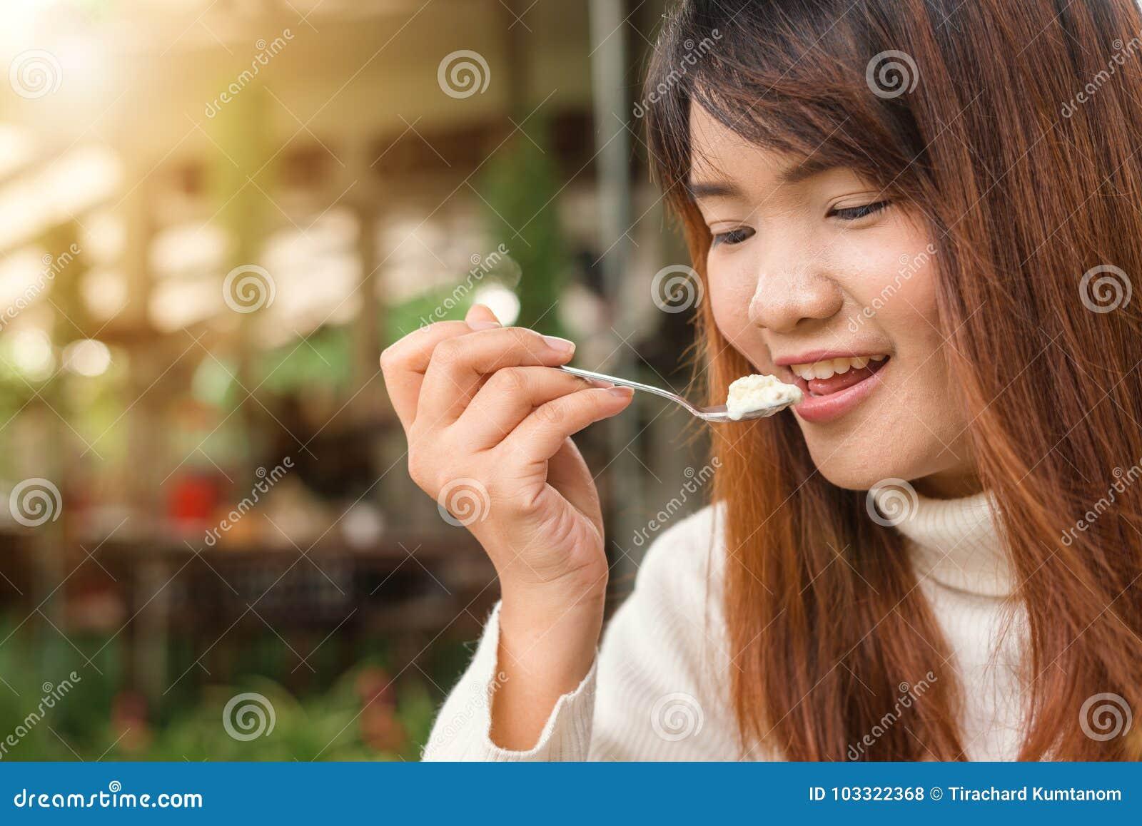 Привлекательная счастливая милая молодая азиатская женщина сидя и есть десерт на кафе outdoors Еда, поп-еда, кулинарное, печь и п