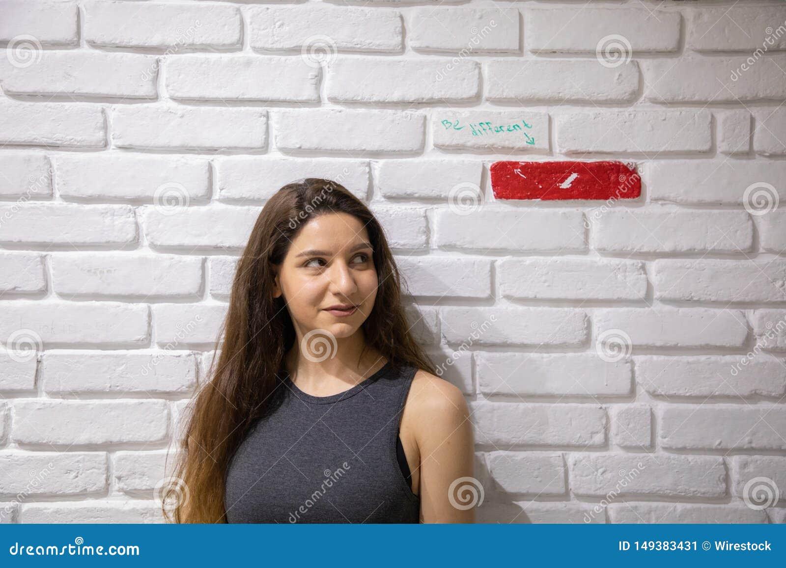 Привлекательное женское модельное положение около белой кирпичной стены с одиночным красным кирпичом