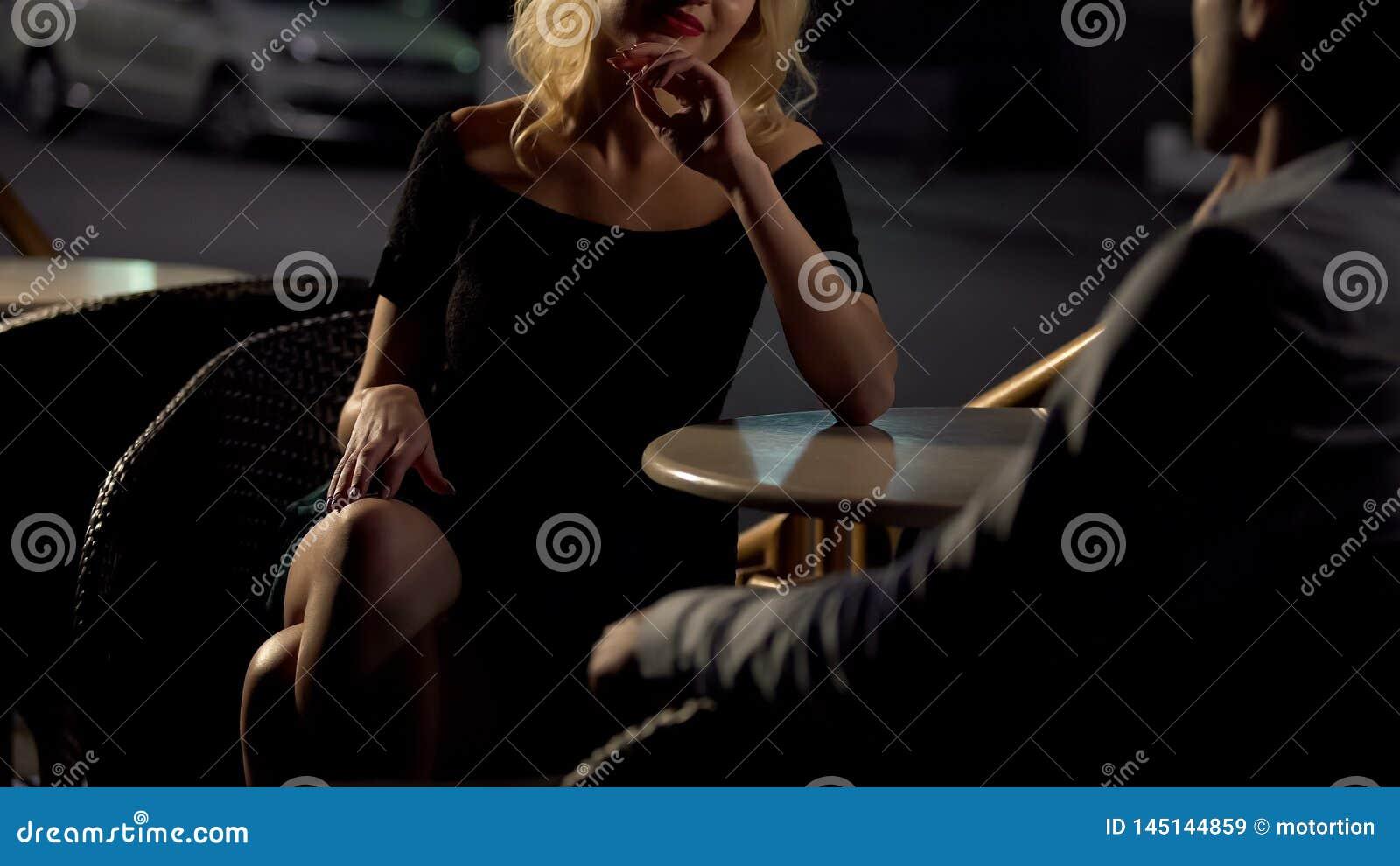 Привлекательный белокурый женский сокращая человек на террасе ресторана, эскорт услуги